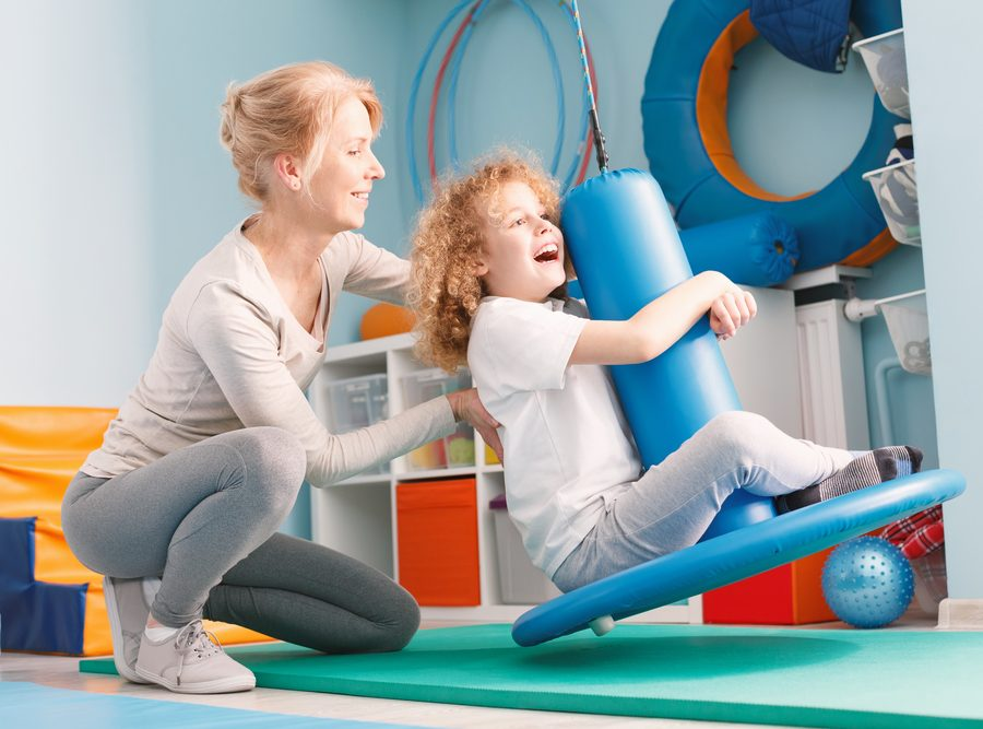 Child doing balance exercises on therapeutic swing